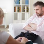 Addicted businessman talking with psychiatrist on psychotherapy session